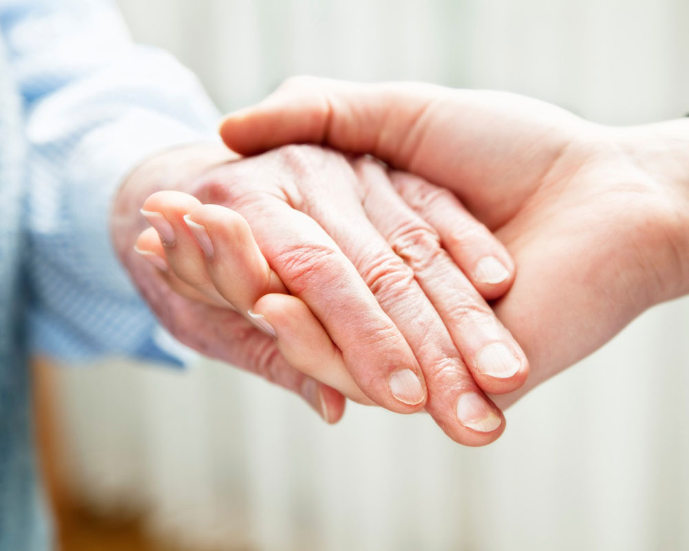 Aging with Dignity Services - Photo of an elderly woman's hand holding someone else's hand for support