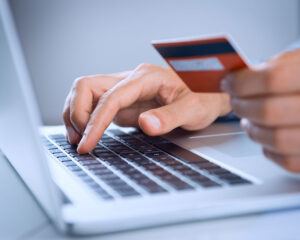 Donate Online - Photo of someone's hands holding a credit card in front of a laptop computer