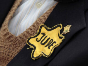 Reparations - Photo of an elderly Holocaust survivor's jacket lapel with a yellow star on it