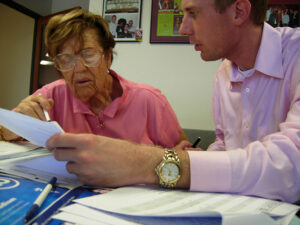 Homeowner Protection & Fraud Prevention - Photo of an elderly woman homeowner meeting with a lawyer