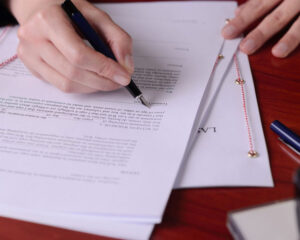 Planned Giving - Photo of someone's hands signing a legal document