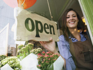 "Small Business Development Project - Photo of a female small business owner with an ""Open"" sign in her business window"