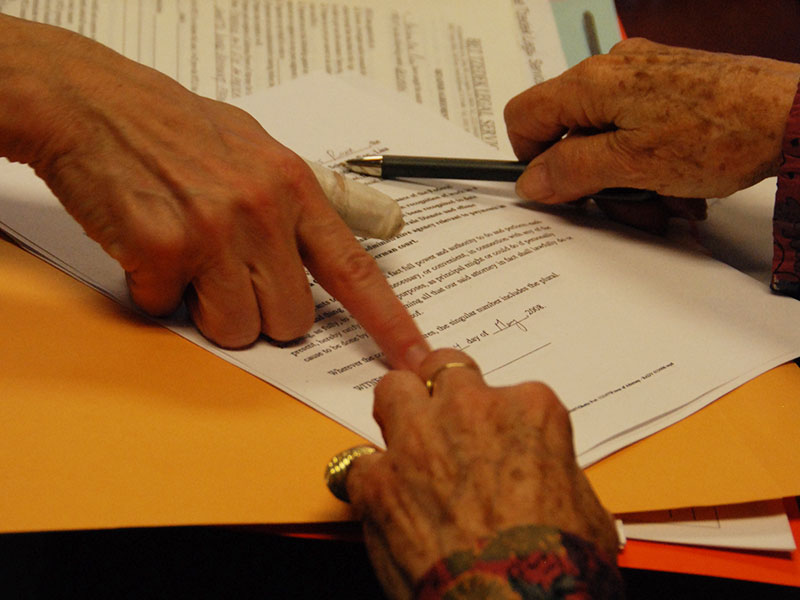 Low-Income Taxpayer Clinic - Photo of two women's hands pointing at a tax document