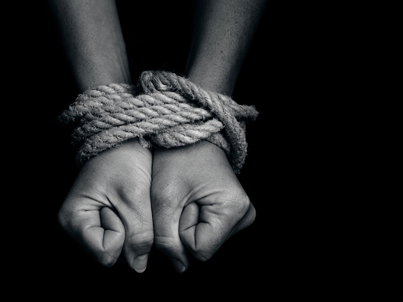 Help for Trafficking Survivors - Photo of a woman's hands bound by rope
